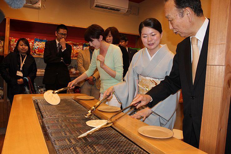 手焼きせんべいを体験するミライズの穴沢恵子代表(右から2人目)ら=28日、新発田市月岡温泉