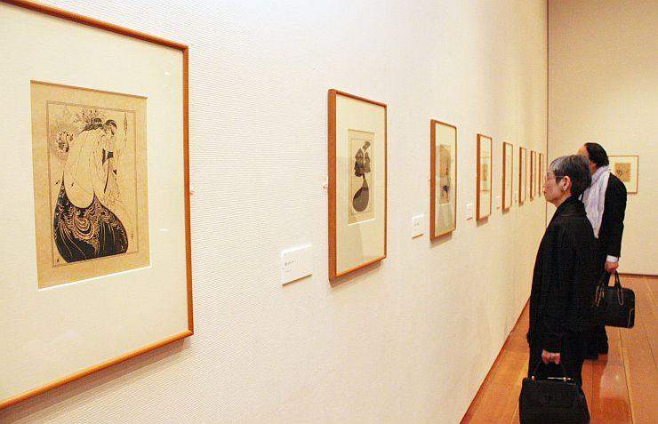 ずらりと並んだビアズリーの挿絵を眺める関係者ら=28日、新潟市中央区万代島