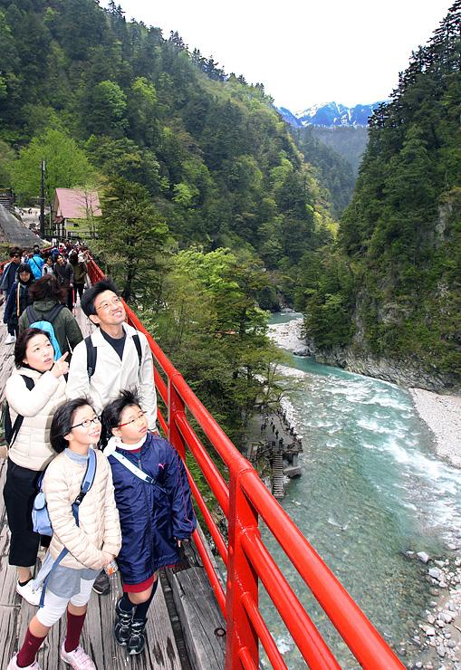 奥鐘橋から新緑と清流の眺めを楽しむ観光客。右奥にはサンナビキ山が見えた=黒部峡谷・欅平