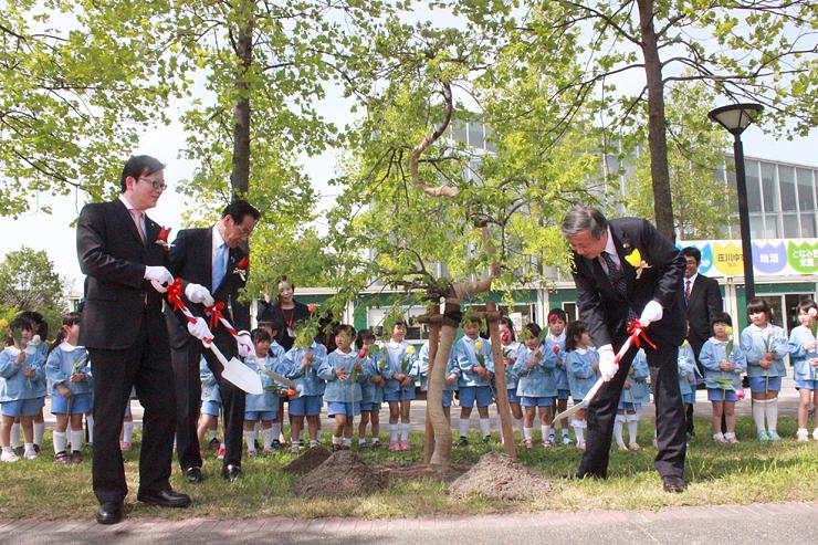 白梅を植樹する(手前右から)夏野砺波市長、村岡市議会議長、洪部長=チューリップ四季彩館前
