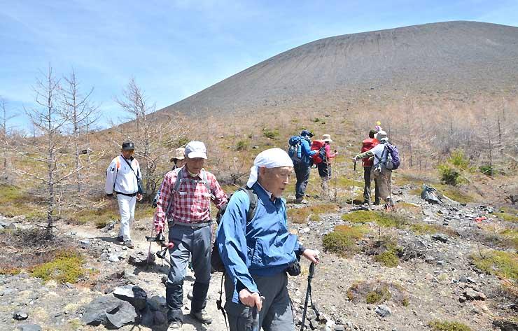立ち入り可能区域で最も奥の賽の河原を歩いたり、前掛山(奥)を眺めたりする登山者たち
