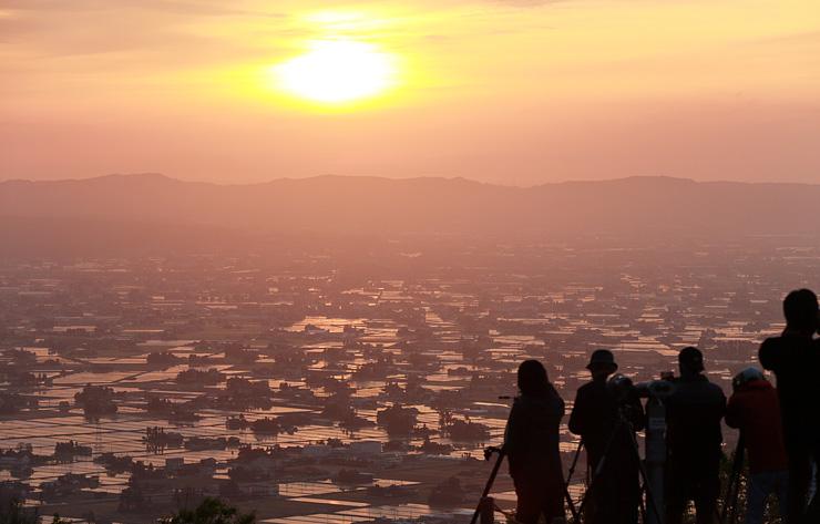 夕日を受けてピンク色に染まる散居村の水田。大勢の写真愛好家が訪れた=8日午後6時35分ごろ、砺波市庄川町隠尾の散居村展望広場から