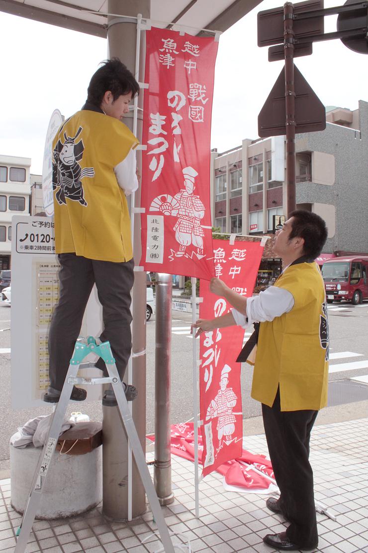 「うおづ戦国のろし祭り」をPRするのぼりを立てる市職員=あいの風とやま鉄道魚津駅前