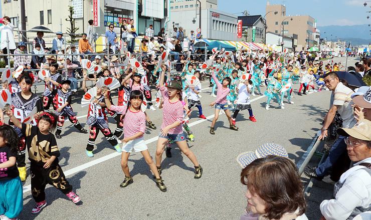 扇子を手に「よっしゃ来い!!CHOUROKU」の総踊りを披露する参加者=魚津駅前通り