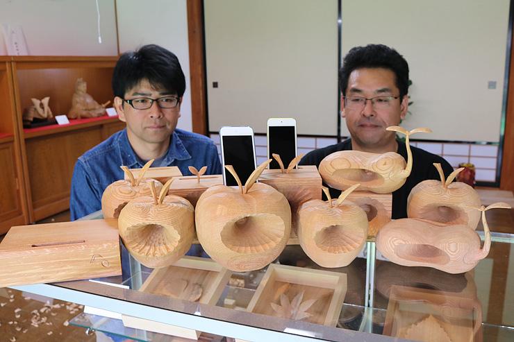 リンゴやソラマメ型の木彫スピーカーを並べる伊藤さん(右)と久保さん