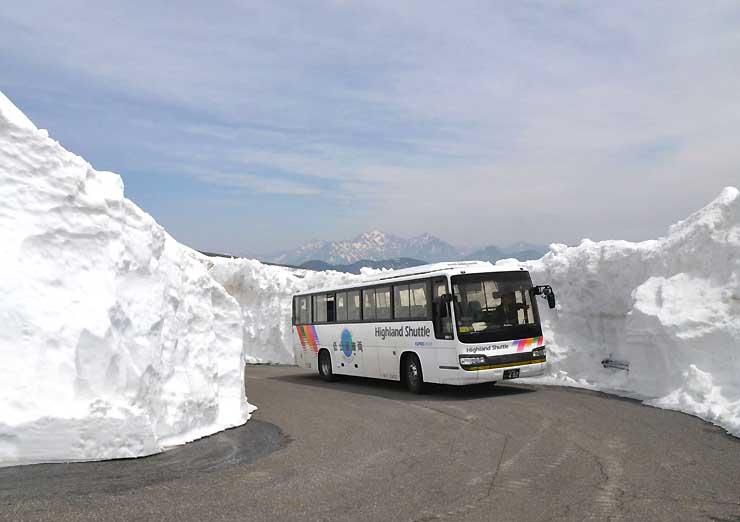除雪を終えた県道で、雪の壁の間を試運転する「春山バス」