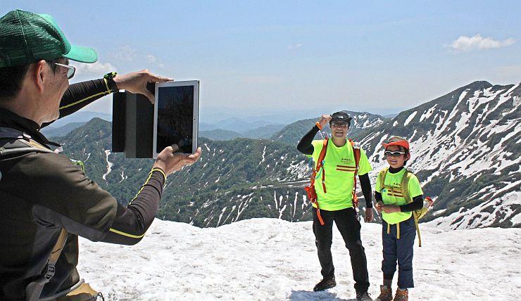 守門岳主峰の一つ大岳から山々を背景に記念撮影を楽しむ親子連れら=22日、守門岳