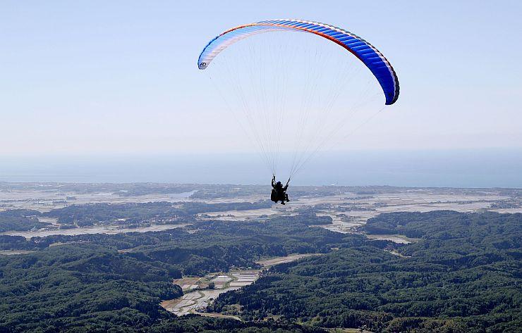 パラグライダーの観光フライトで空を飛ぶ記者=上越市吉川区の尾神岳