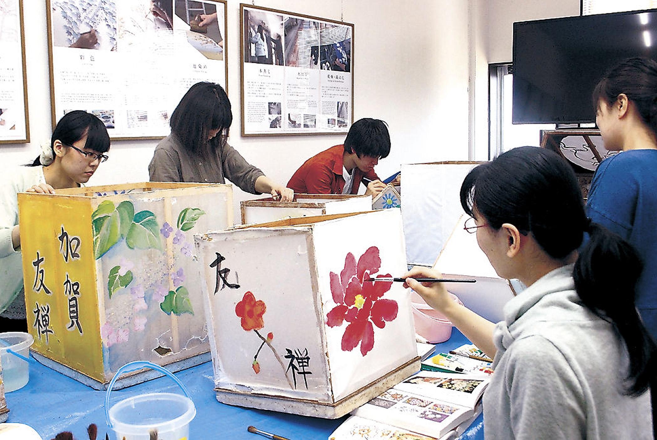 燈ろうの絵付けに取り組む弟子と学生=専光寺町の加賀友禅染色団地