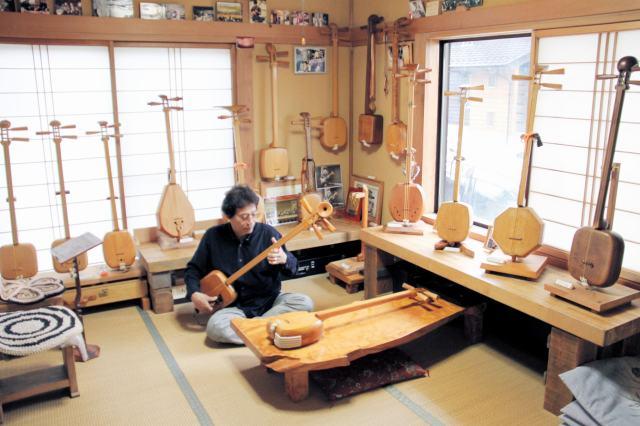 ヒノキなどさまざまな木材で製作した三味線を展示している野村さんの工房=福井市