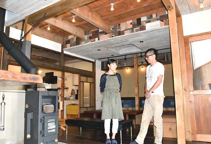 完成したゲストハウスのオープンスペースに立つ(右から)小沢さんと妻の智子さん
