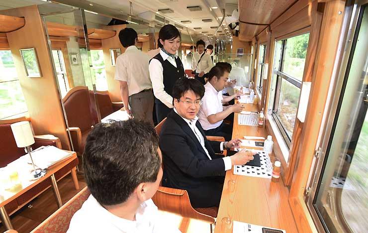 観光列車「ろくもん」のクルーズトレインの試乗会で車窓の景色を楽しむ参加者たち
