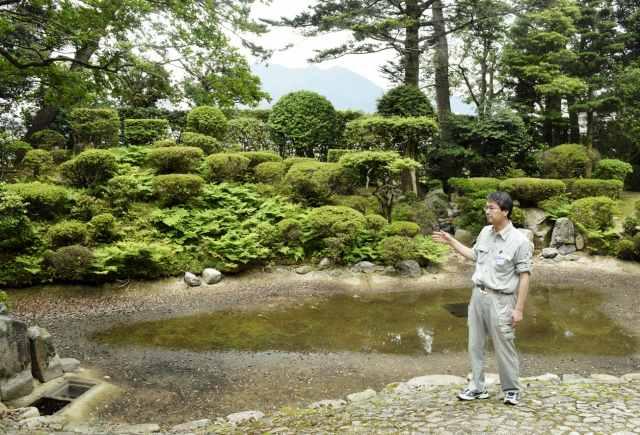 水抜きされた柴田氏庭園。見学会では庭の特徴について説明する=26日、福井県敦賀市市野々町1丁目