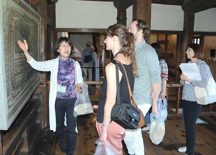 松本城の歴史を外国人観光客に英語で伝える中田さん(左)とその様子を学ぶ黒岩さん(右)