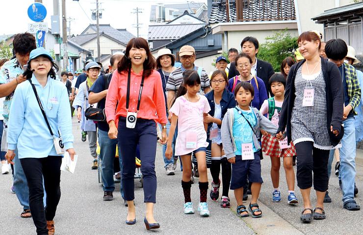 高橋さんとまち歩きを楽しむ参加者=黒部市生地