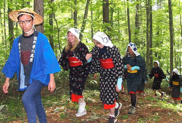 工女の衣装や法被を着て、野麦峠を目指して歩く留学生たち