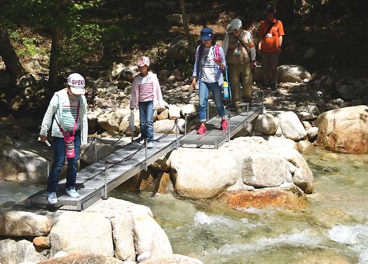 乳川に架かる橋を渡って河畔探勝エリアに入る参加者たち