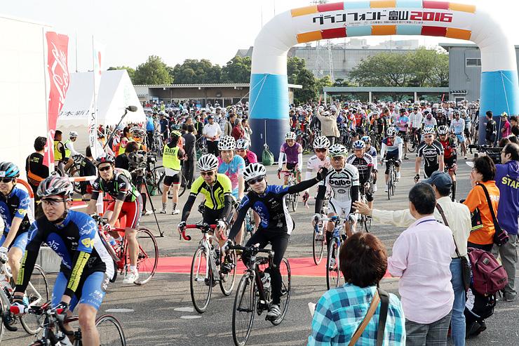 ゲートをくぐり抜け次々とスタートするロングコースの参加者=富山競輪場