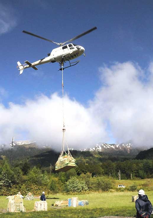 御嶽山(奥)の山小屋などに向け、荷物を運ぶヘリコプター=31日午前7時18分、木曽町