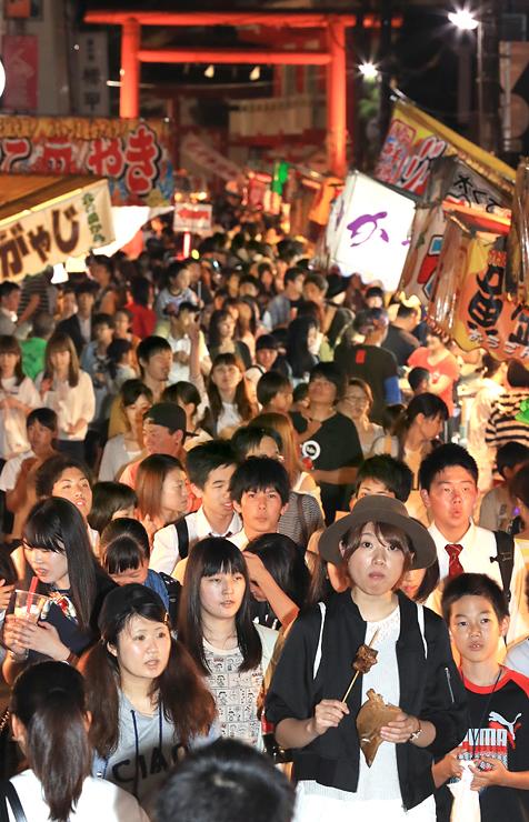 日枝神社の鳥居につながる通りは露店が並び、大勢の人々でにぎわった=富山市山王町