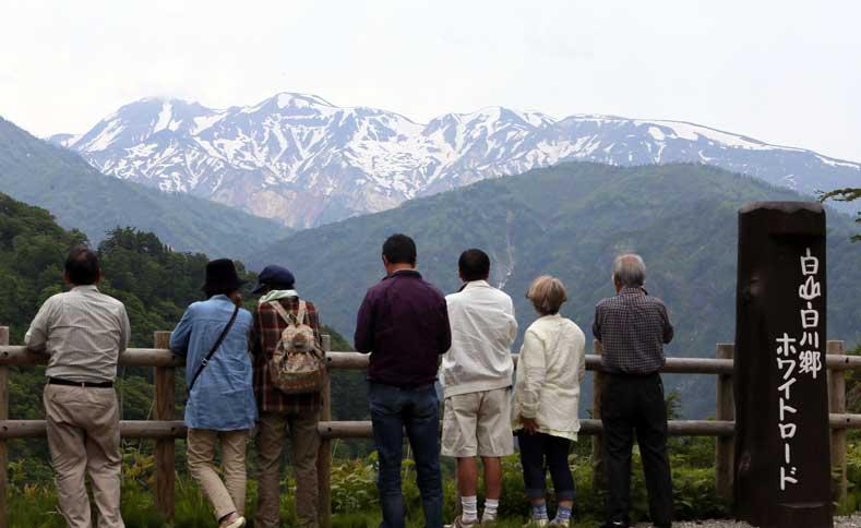 雪の残る雄大な白山を一望する利用客=白山白川郷ホワイトロードの栂の木台駐車場