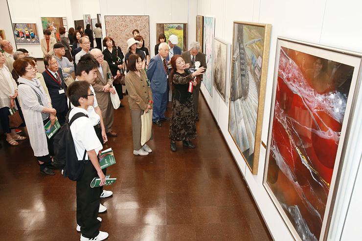洋画部門で遠藤さん(右)の講評を聞きながら作品を鑑賞する来場者=県民会館