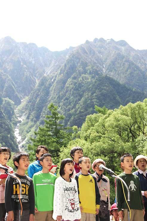 山々を背景にウェストン祭で合唱する小学生ら
