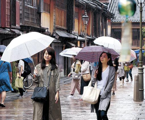 雨の中、ひがし茶屋街を散策する観光客=金沢市東山1丁目