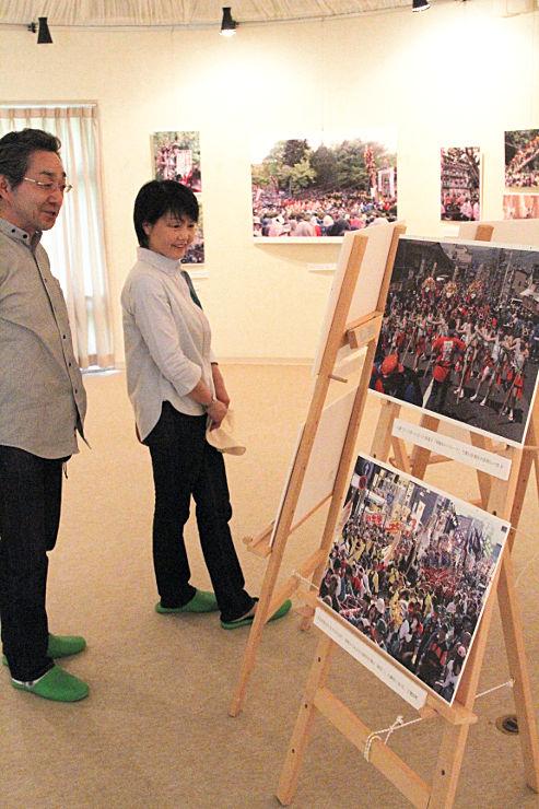 諏訪大社御柱祭の熱気を伝える写真を見て回る来館者