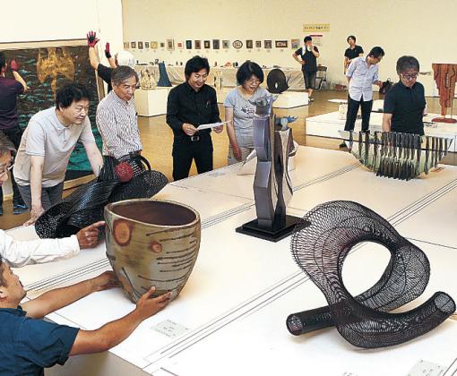 開幕に向け、陳列作業を進める石川会のメンバー=金沢21世紀美術館