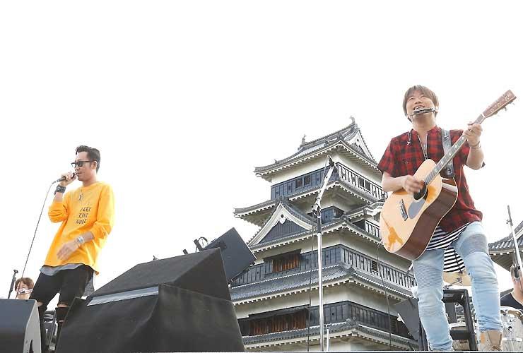 天守を背景に映画「orange」の主題歌「未来」などを歌い上げる小渕さん(右)と黒田さん
