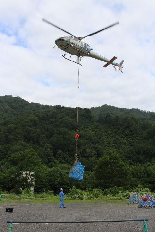 荷上げ作業で山小屋に飛び立つヘリ=15日、胎内市下荒沢