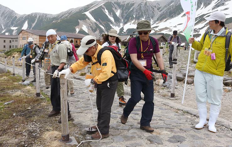 ライチョウ保護柵のロープを張るサポート隊の隊員=立山・室堂平