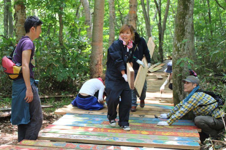 汗を流しながら、木道の整備作業に励む参加者=18日、湯沢町三国