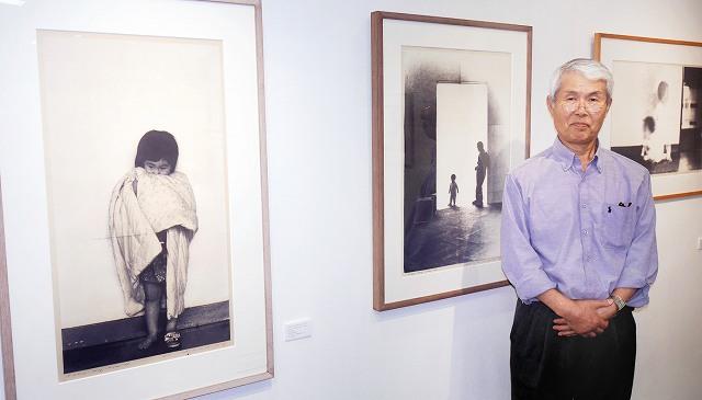 版画家の野田哲也さんと作品「日記」シリーズ。国際展大賞受賞作など約30点が展示されている=福井市