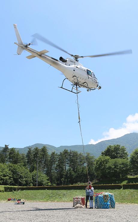 鳩吹公園で山荘に運ぶ荷物を引き上げるヘリコプター=21日、伊那市