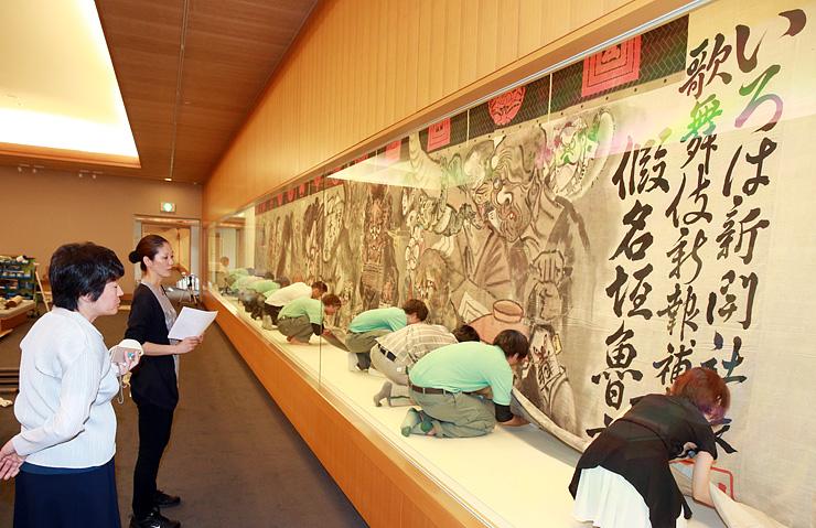 横17メートルに及ぶ大作を慎重に展示するスタッフら=県水墨美術館