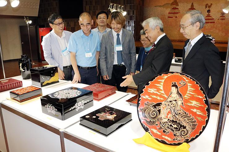 高岡市内の関係者と一緒に、出品作を見て回る王代表(左)ら=高岡地域地場産業センター