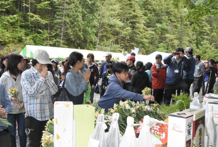 竹沢長衛の碑の前に花を供える長衛祭の参加者