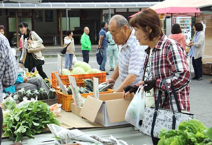 軽トラックの荷台に商品が並ぶ「軽トラ市」に訪れた人たち
