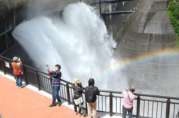 黒部ダムで始まった観光放水を新展望テラス(手前)から眺める観光客