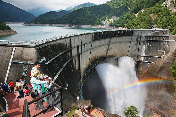 観光放水が始まった黒部ダムと晴れ間に浮かび上がった虹。中央下は「新展望テラス」=立山町芦峅寺