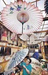 夏向けの涼しげな絵柄の和傘が並ぶ工房=金沢市千日町