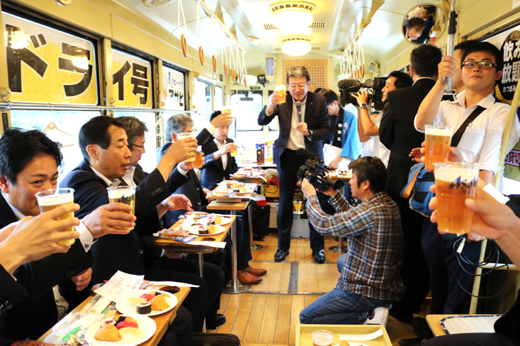 ビア電の試乗会で乾杯する参加者=富山市内