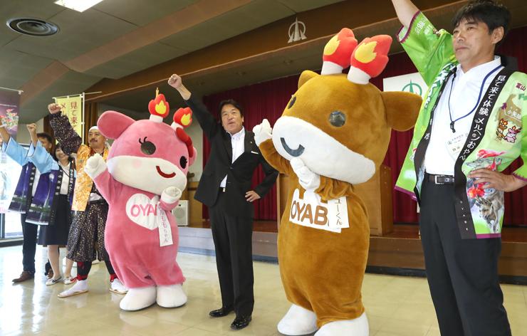 遠征成功を誓い、こぶしを挙げる遠征隊のメンバーと桜井市長(中央)