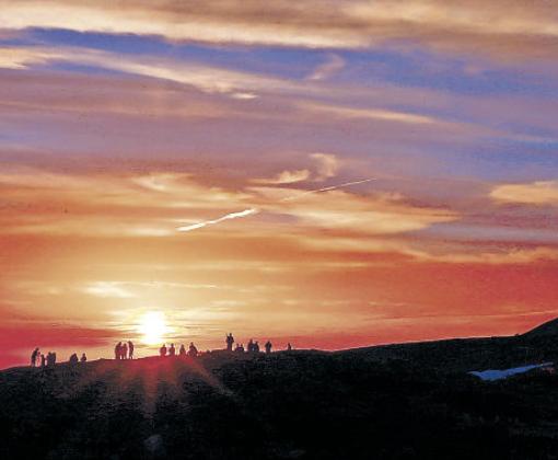 沈む夕日を見守る登山客=30日午後7時、白山室堂ビジターセンター周辺(三上聡一撮影)