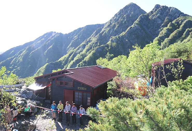 塩見岳西峰(最も高い峰)を背に、テープカットがあった塩見小屋=1日午前7時38分