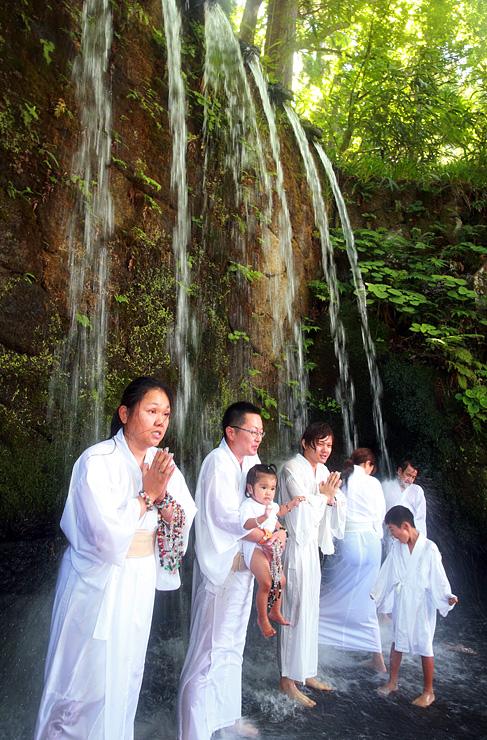 六本滝に打たれる信者たち=大岩山日石寺