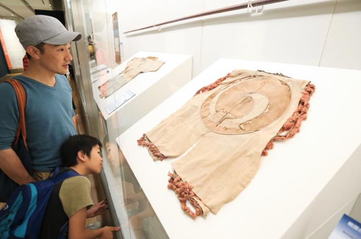 上田会場だけで展示する「血染めの陣羽織」を見る親子