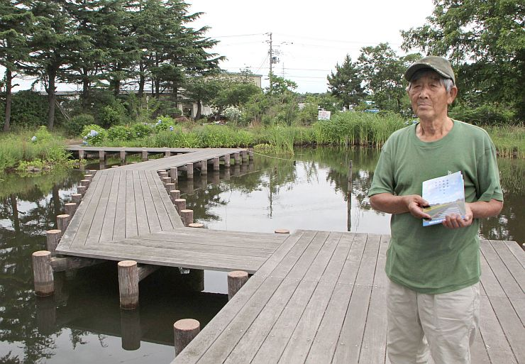 北区の8カ所の水辺を巡るスタンプラリーの冊子を紹介する藤田八郎さん=新潟市北区濁川の自然生態観察園